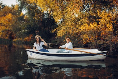 Love couple in boat on quiet lake, side view
