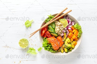 Buddha lunch bowl with grilled salmon fish, vegetables, lettuce salad and rice