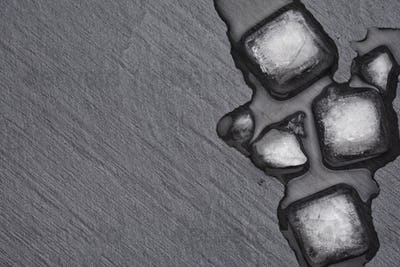 Melting ice cubes on the black slate with copy space