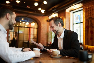 Business People Signing Contract in Restaurant