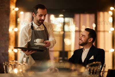 Smiling Waiter Bringing Coffee to Guest in Restaurant