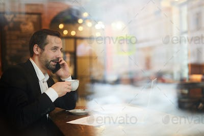 Smiling Mature Businessman Working in Cafe