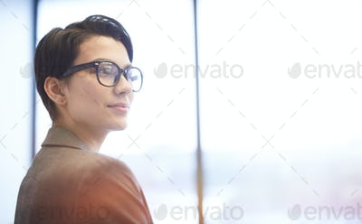 Smiling Young Businesswoman Standing by Window