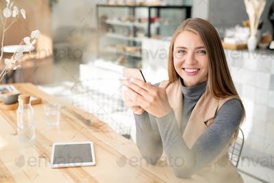 Pretty student or businesswoman in smart casual using mobile gadgets