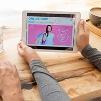Young female holding digital tablet with online shop home page on its displa