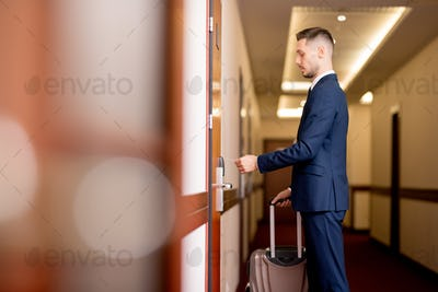 Young businessman holding plastic card by door while going to enter the room