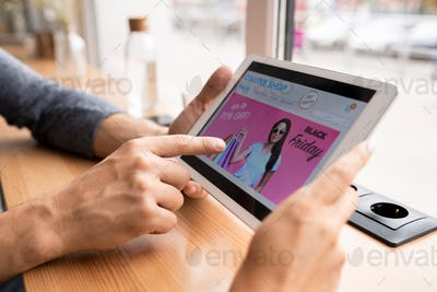 Hand of young man pointing at touchpad display while going to enter online shop