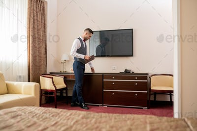 Young elegant hotel porter with touchpad touching piece of wooden furniture