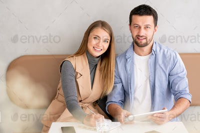 Small group of young successful employees in casualwear working by table in cafe