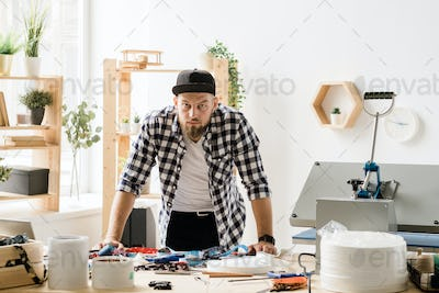 Young casual craftsman looking at you while bending over table during work