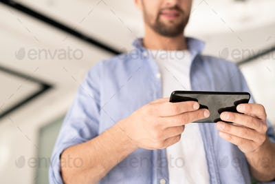 Young businessman in casualwear holding smartphone while watching something