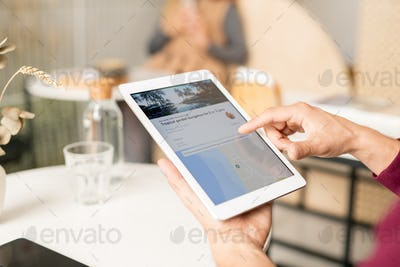 Male hand over tablet screen scrolling through travel website