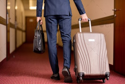 Young businessman in suit carrying black leather handbag and pulling suitcase
