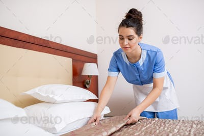 Pretty young brunette chamber maid in blue uniform making bed in hotel room