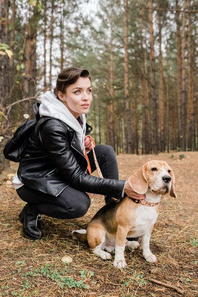 Pretty young brunette woman cuddling cute beagle puppy while sitting on squats