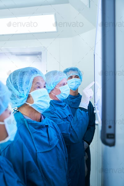 Surgeons checking patients data on led screen