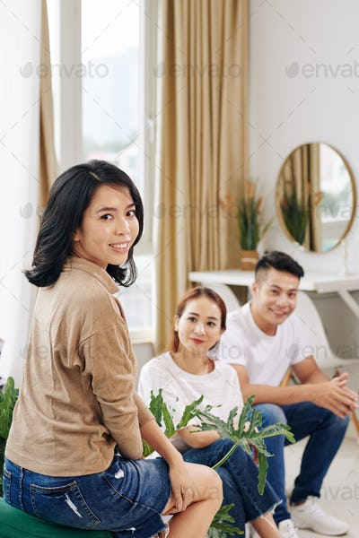 Pretty Asian woman attending meeting with friends