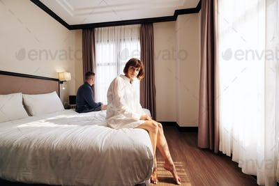 Pretty woman sitting on hotel bed