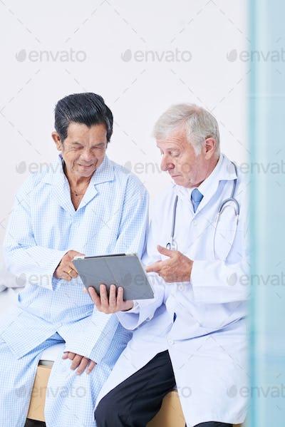 Doctor showing prescription to senior patient