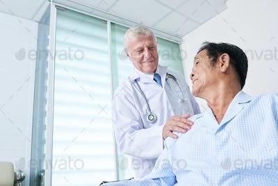 General practitioner patting shoulder of senior patient