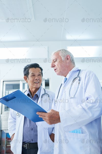 Doctor listening to coworker reading medical history