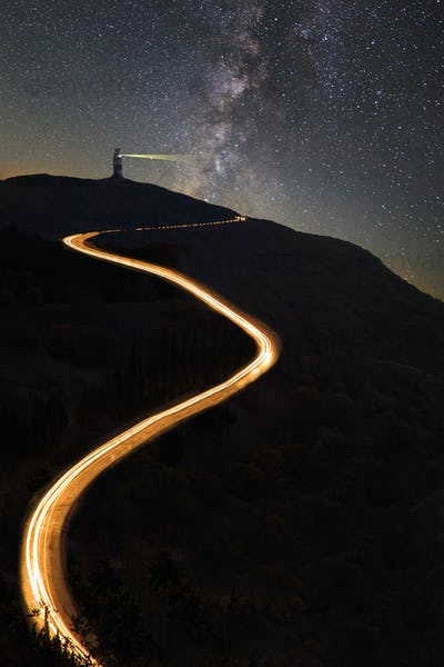 Road in the mountains under the Milky Way