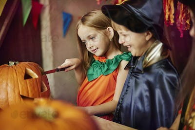 Children affectionated with carving a pumpkin