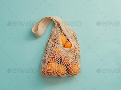 Mesh bag with fruits on blue background.Zero waste