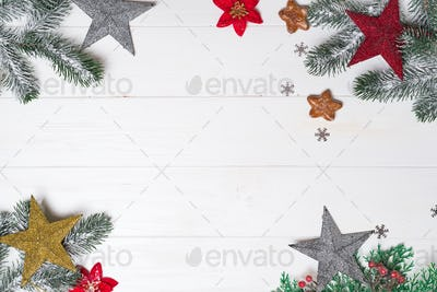 Fir tree branch and toys stars on white wooden, top view copy space