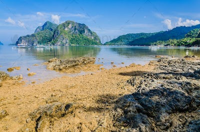 Stony beach during low tide in front of huge rocks in Background, El Nido, Palawan, Philippines