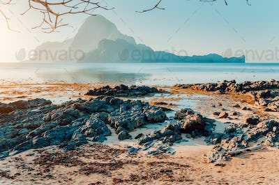 Rocky Beach during low tide in morning light in front of amazing Cadlao Island, El-Nido, Palawan