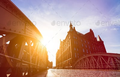 Silhouette of Bridge and Buildings in evening sun rays in low angle view. Speicherstadt Hamburg
