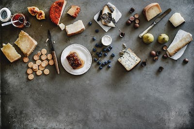 Variety of wine snacks and cheeses over grey background