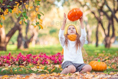 Little adorable girl with pumpkin outdoors on a warm autumn day