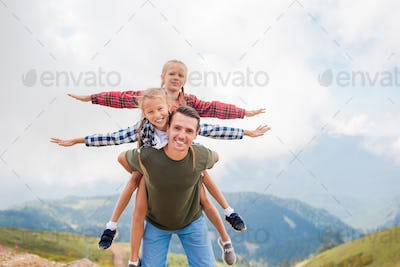 Beautiful kids and happy man in mountains in the background of fog
