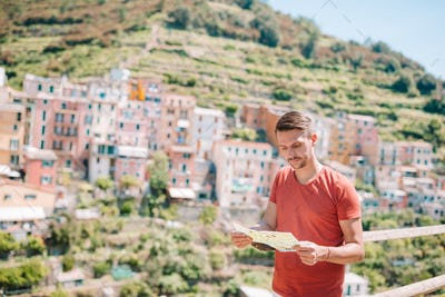 Young man tourist with map background stunning villag, Manarola, Cinque Terre, Liguria, Italy