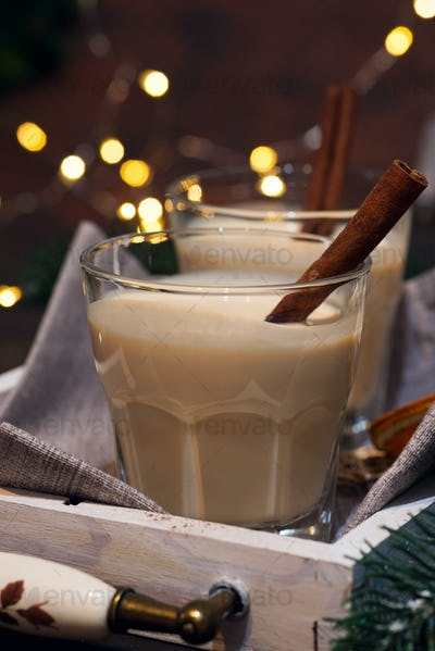 Homemade White Holiday Eggnog with a Cinnamon Stick on dark background with light bokeh . Christmas