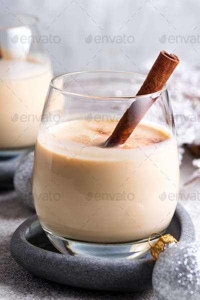 Winter spicy hot drink eggnog in a glasses with cinamon in stone plate, ice frost branches on light