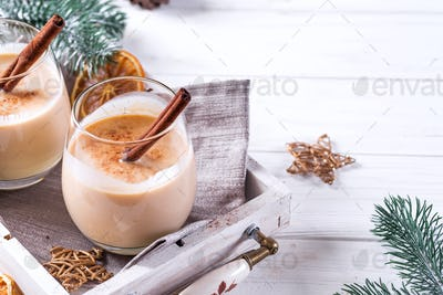 Winter spicy hot drink eggnog in a glasses with cinamon in tray, dry orange,fir branches and pine