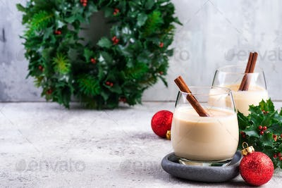 New Year or Christmas Eggnog cocktail - hot winter or autumn drink with cinnamon and nutmeg in a
