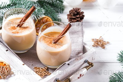Eggnog in glasses with cinamon in tray, dry orange,fir branches and pine cone on white wooden table