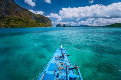 Island hopping Tour boat hover over open blue ocean water between exotic karst limestone islands on