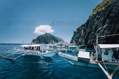 Tourist banca boats on blue sea water surface on island hopping tour. El Nido, Palawan, Philippines