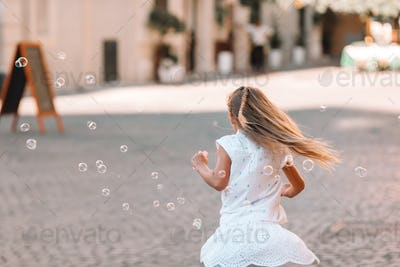 Adorable little girl blowing soap bubbles in Trastevere in Rome, Italy