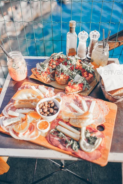 Tasty italian snack. Fresh bruschettes, cheeses and meat on the board in cafe with amazing view
