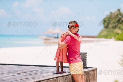Family of father and sporty little girl having fun on the beach