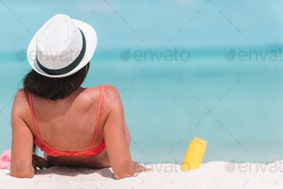Beautiful young woman holding a suncream lying on tropical beach
