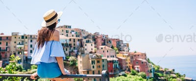Young woman with beautiful view at old village in Cinque Terre, Liguria, Italy