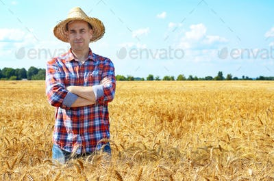 Happy looking farmer in straw hat stands at harvest ready wheat