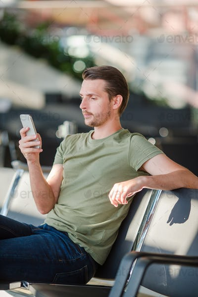 Passenger in a airport lounge waiting for flight aircraft. Young man with cellphone in airport